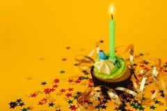 Geburtstagskleiner kuchen mit Kerze auf gelbem Hintergrund Stockfotografie