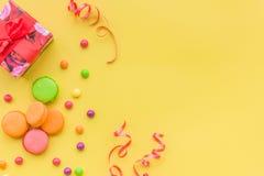 Geburtstagskonzept mit eingewickeltem Geschenk und Bonbons auf gelbem copyspace Draufsicht des Hintergrundes Stockbilder