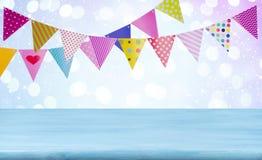 Geburtstagskonzept mit Holztisch, Girlanden und Zusammenfassung beleuchtet Hintergrund Lizenzfreie Stockfotos