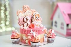 Geburtstagskuchen für 3 Jahre verziert mit Schmetterlingslebkuchenkätzchen mit Zuckerglasur und der Nr. drei Meringe blaß - Rosa  lizenzfreie stockfotos