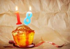 Geburtstagskuchen mit brennenden Kerzen als Nr. achtzehn Lizenzfreie Stockfotografie