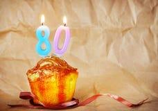 Geburtstagskuchen mit brennenden Kerzen als Nr. achtzig Lizenzfreie Stockfotografie