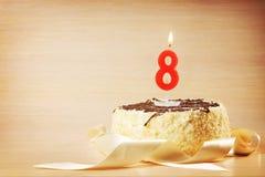 Geburtstagskuchen mit brennender Kerze als Nr. acht Lizenzfreies Stockfoto