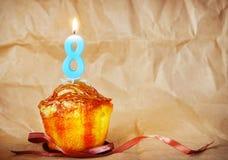 Geburtstagskuchen mit brennender Kerze als Nr. acht Stockbilder