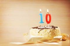 Geburtstagskuchen mit brennender Kerze als Nr. zehn Stockfotos