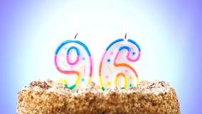 Geburtstagskuchen mit einer brennenden Geburtstagskerze Nr. 96 Hintergrund ändert Farbe stock video