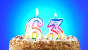Geburtstagskuchen mit einer brennenden Geburtstagskerze Nr. 63 Hintergrund ändert Farbe stock video