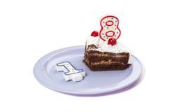 Geburtstagskuchen mit zwei Kerzen und Stück des Kuchens Stockbild