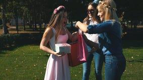 Geburtstagsmädchen empfängt Glückwünsche und Geschenke von den Freundinnen Alle sind elegant angekleidet und froh freundlich stock footage