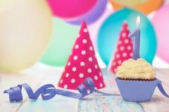 Geburtstagsmuffin, Ausblasen und Parteihüte stockbilder