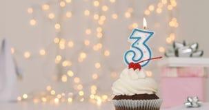 Geburtstagsschalenkuchen mit Zahl drei Kerze stock footage