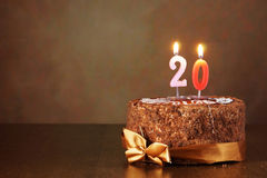 Geburtstagsschokoladenkuchen mit brennenden Kerzen als Nr. zwanzig Stockbilder