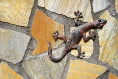 Gecko made of metal on a stone wall Stock Photos