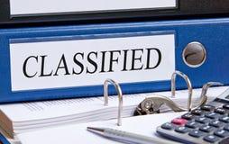 Geclassificeerd - blauw bindmiddel met tekst op bureau in het bureau stock afbeeldingen