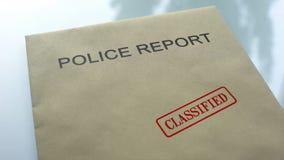 Geclassificeerd politierapport, gestempelde verbinding over omslag met belangrijke documenten stock fotografie