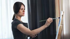 Geconcentreerd aantrekkelijk jong de tekeningsbeeld van de kunstvrouw op canvas die borstel middelgroot schot gebruiken stock video
