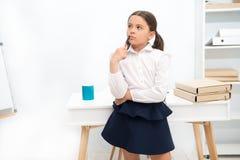 Geconcentreerd bij zich het herinneren Het kindmeisje draagt school eenvormige status met het herinneren van gezichtsuitdrukking  royalty-vrije stock fotografie