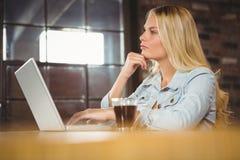 Geconcentreerd blonde die koffie hebben en laptop met behulp van royalty-vrije stock foto's
