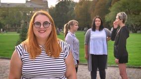 Geconcentreerd bruto Kaukasisch wijfje in fron van groep feministes die met vertrouwen glimlachen openlucht stock videobeelden