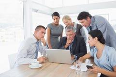 Geconcentreerd commercieel team die aan laptop werken stock fotografie