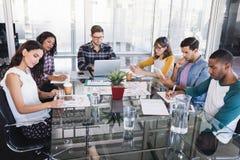 Geconcentreerd creatief commercieel team die rond glaslijst werken Stock Afbeeldingen