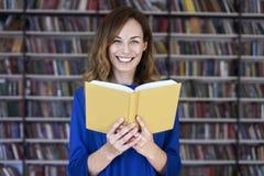 Geconcentreerd en slim portret van vrouw meer dan 25 in een bibliotheek die een geopend boek lezen, Jonge student in mede-werkt stock foto