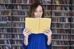 Geconcentreerd en slim portret van vrouw meer dan 25 in een bibliotheek die een geopend boek lezen, Jonge student in mede-werkt,  royalty-vrije stock foto's