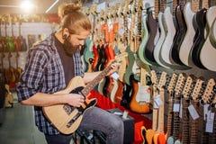 Geconcentreerd jong musicustribune en spel op elektrische gitaar Hij bekijkt het De kerel is in muziekwinkel Jonge hipster royalty-vrije stock afbeeldingen