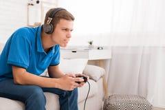 Geconcentreerd kerel het spelen videospelletje met bedieningshendel stock fotografie