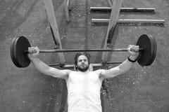 Geconcentreerd op oefening Mensenatleet opleiding met barbell De atletische mens verhoogt zware barbell Atleten spierlichaam stock afbeelding