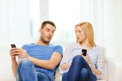 Geconcentreerd paar met smartphones thuis royalty-vrije stock foto's
