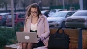 Geconcentreerd uitvoerend wijfje die freelancer het verre werk aangaande laptop in openlucht in avond doen stock footage