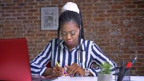 Geconcentreerde Afrikaanse vrouw het schrijven nota's en het zitten bij de werkplaats dichtbij rode laptop op baksteenachtergrond