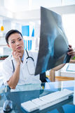 Geconcentreerde arts die Röntgenstralen analyseren Stock Foto