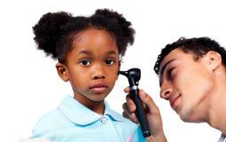 Geconcentreerde arts die zijn jonge patiënt onderzoekt Stock Foto's