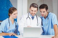 Geconcentreerde artsen die laptop met behulp van terwijl status bij bureau royalty-vrije stock afbeeldingen