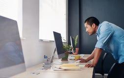 Geconcentreerde Aziatische ontwerper die aan een computer in een bureau werken royalty-vrije stock foto