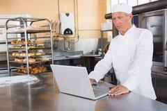 Geconcentreerde bakker die laptop op worktop met behulp van royalty-vrije stock foto