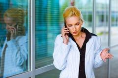 Geconcentreerde bedrijfsvrouw die op mobiel spreekt Stock Fotografie