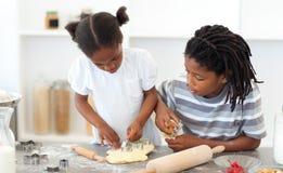 Geconcentreerde broer en zuster kokende koekjes Stock Foto