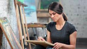 Geconcentreerde deskundige vrouwelijke schilder die het schetsen maken gebruikend potlood die bij kunststudio werken stock footage