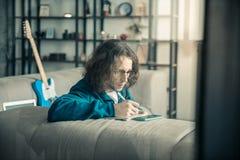 Geconcentreerde donker-haired jonge mens die ernstig terwijl het vullen van notitieboekje zijn stock foto's