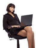 Geconcentreerde donkerbruine vrouw in donkere kledingszitting Royalty-vrije Stock Foto