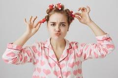 Geconcentreerde gehinderde jonge dame in comfortabele pyjama met en lippen fronsen vouwen, haar-krulspelden opstijgen en harten d stock afbeeldingen