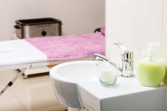 Geconcentreerde gootsteen met kaars in beautician spa salon stock foto