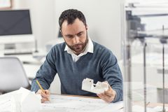 Geconcentreerde ingenieurs veranderende blauwdruk volgens 3D model Stock Foto's