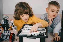 geconcentreerde jonge geitjes die diy robot, stam construeren stock afbeeldingen