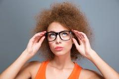 Geconcentreerde jonge krullende vrouw die in zwarte glazen omhoog kijken Royalty-vrije Stock Afbeelding