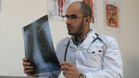 Geconcentreerde jonge mannelijke arts die borst xray beeld onderzoeken stock afbeeldingen