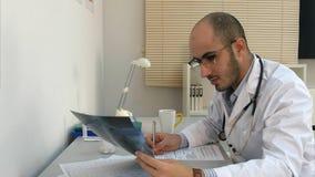 Geconcentreerde jonge mannelijke arts die xray beeld onderzoeken en vorm invullen stock foto's